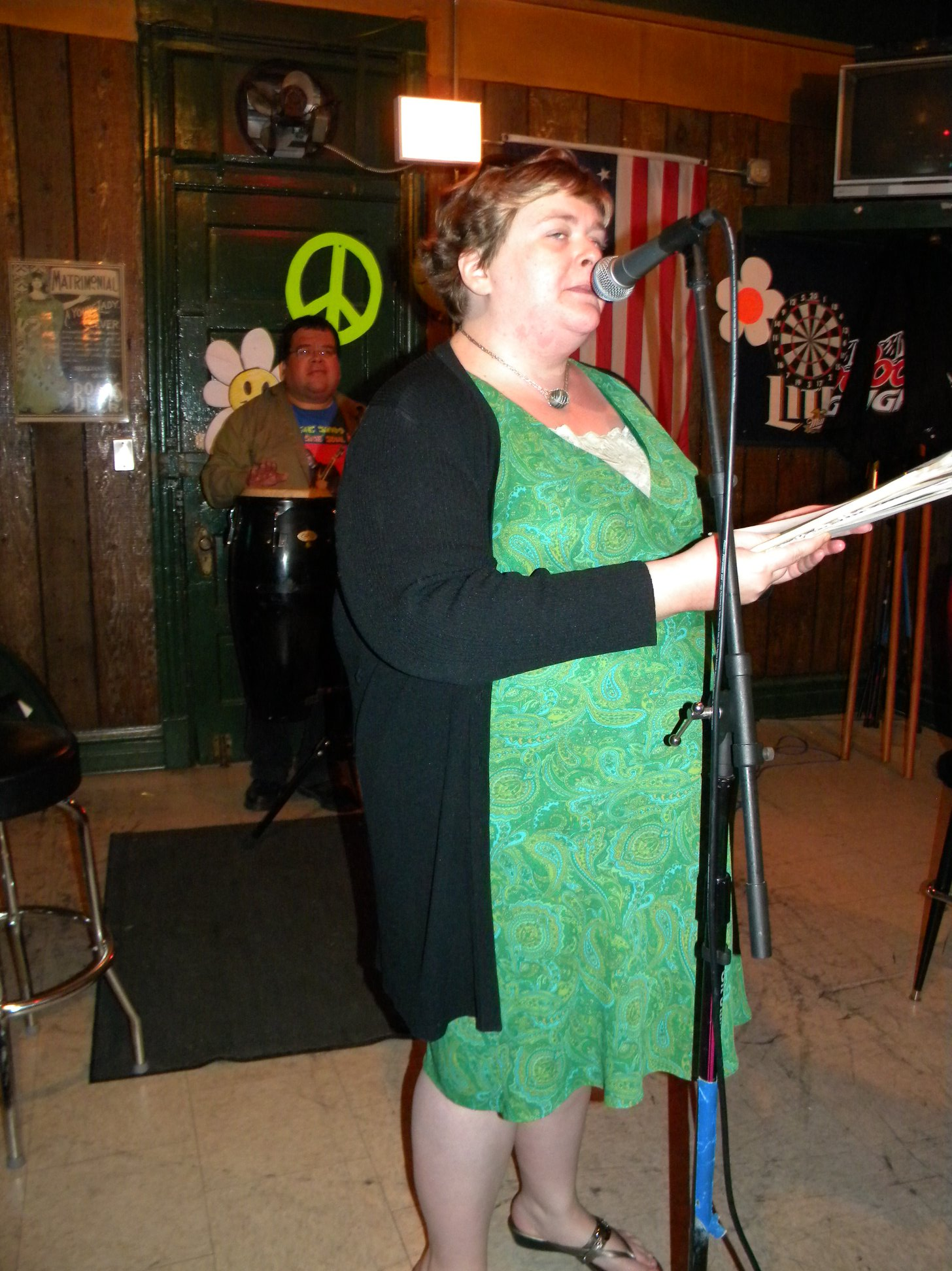 A photo of me standing at a mic in a green knee-length dress with a black cardigan, reciting poety at an open mic night. A man stands in the background in front of a green peace sign.
