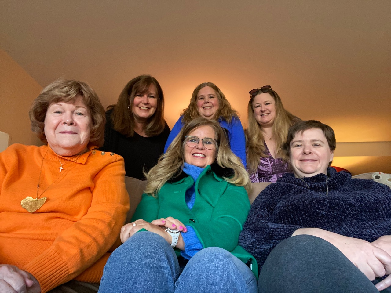 A photo of six women with three sitting on the couch and three standing behind them.