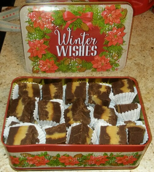 "A photo of peanut butter fudge pieces in a tin stating ""Winter Wishes"""